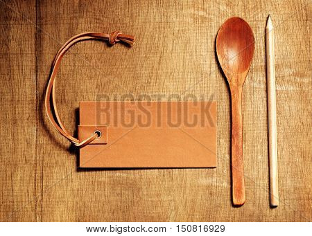 Wooden spoon on wood table background with leather blank for recipe