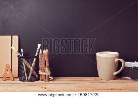Website header design with designer vintage desk over chalkboard background