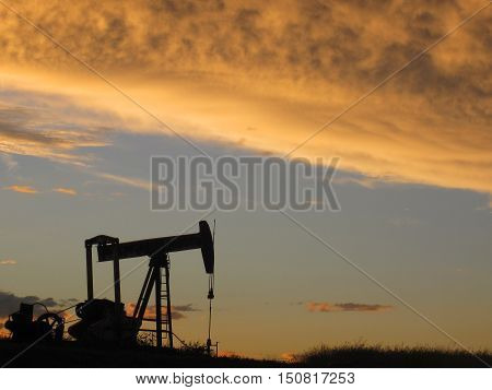 Single oil pumper jack during an orange sunset