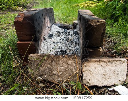 Homemade brazier of old bricks on the grass