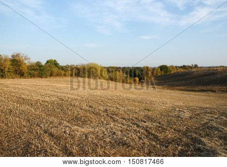 Farming landscape shows the mown field in the autumn at sunset