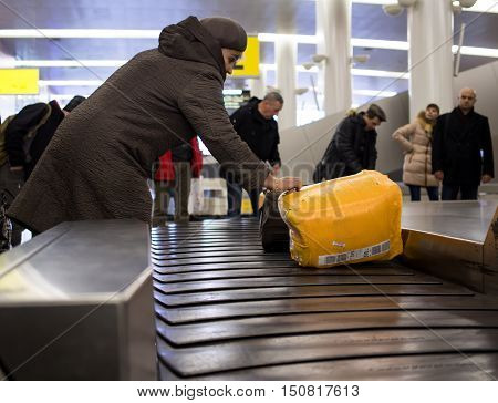 Moscow, Russia - November 07, 2015: People pick up luggage from the conveyor belt conveyor to Sheremetyevo airport.