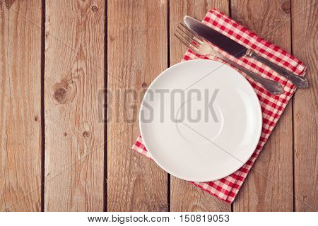 Empty plate with knife and fork on wooden rustic table. View from above. Flat lay