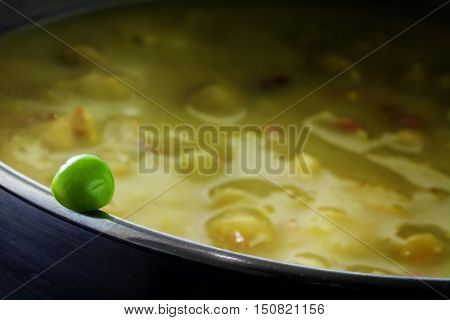 Fresh green pea on the edge of a pot full with overcooked vegetable soup concept for cooking vitamin-preserving or metaphor for a dangerous dare close up with elected focus narrow depth of field