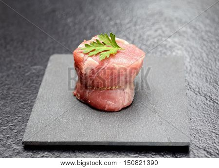 raw fillet medallions of young pork with parsley on a board of black basalt on a gray background