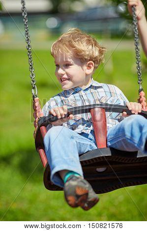 Little blond boy having fun on chain swings