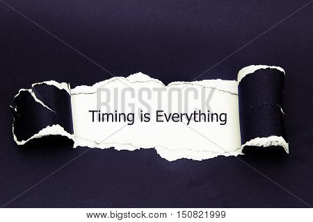 Timing is Everything, appearing behind torn paper.