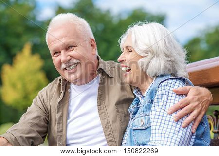 Happy old man and woman are resting in nature together. They are hugging and laughing. Couple is sitting on bench with relaxation