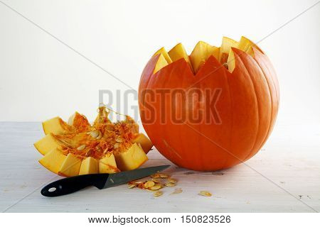 Fresh orange pumpkin cut open with lid and knife on white painted wood copy space
