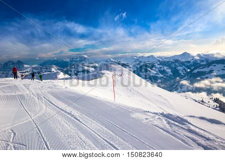 Skiers skiing in Steinbergkogel - Kitzbuehel ski resort with 54 cable cars 170 km prepared skiing slopes and place of famous hahnenkamm races