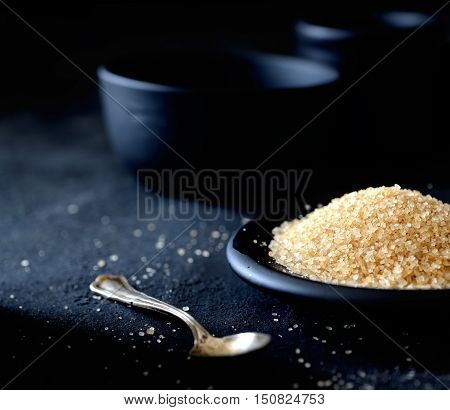Crystals of brown sugar in a saucer, vintage teaspoon on a black background