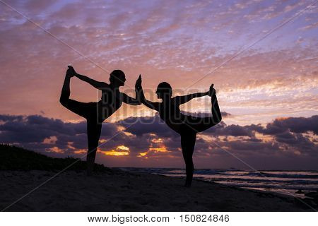 Two women practice yoga at sunrise (Pose: natarajasana)