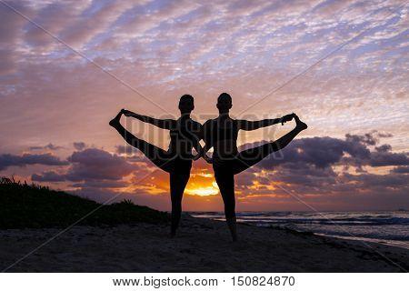 Two women practice yoga at sunrise. (Pose: Utthita Hasta Padangustasana)