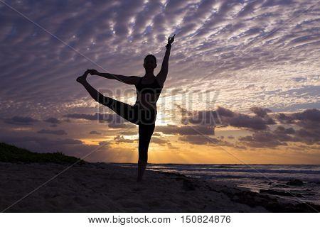 Woman practice yoga at sunrise. (Pose: Utthita Hasta Padangustasana)