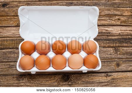 Eggs in molded carton on wooden background