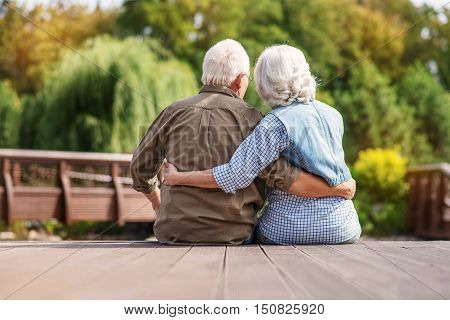 Old man and woman are enjoying nature together. They are sitting and embracing