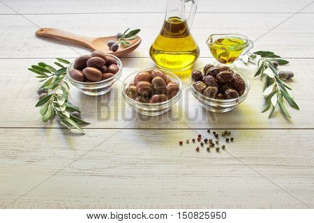 Three kinds of olives in the glass bowls and wooden spoon, olive oil botthe, gravy boat framed by branches of the olive tree on a light white wooden background. Olives and olive oil. Horizontal.