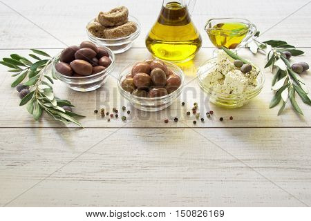 Two kinds of olives, olive oil, feta cheese, crackers framed by branches of the olive tree on a light white wooden background. Olives, olive oil, feta cheese. Horizontal. Daylight.