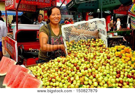 Pengzhou China - October 2 2013: Woman selling Chinese dates and watermelon slices from the back of her pickup truck at the Long Xing outdoor marketplace