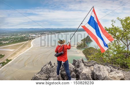 AttractionsKhao Lom Muak at Prachuap Khiri Khan province thailand.Tourists climbing to see the scenery Prachuap Khiri Khan province. The symbol of the conquest of the peak Khao Lom Muak is to raise the flag of Thailand.