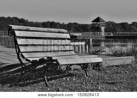 black and white photo of wooden bench at the Alum Lake Kamencove jezero in Chomutov city in the foothills of the Krusne hory Mountains in the Czech Republic