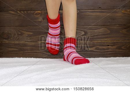 The woman's legs in socks on the rug .Wooden background. Warm , stripey socks.