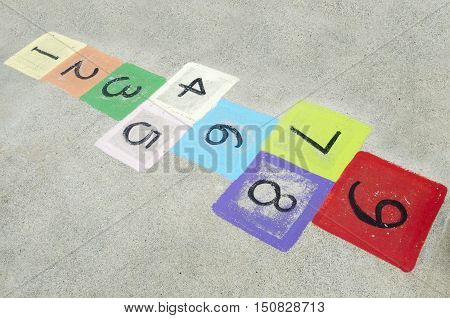 Colorful children's hopscotch on playground concrete. Childhood concept copy space