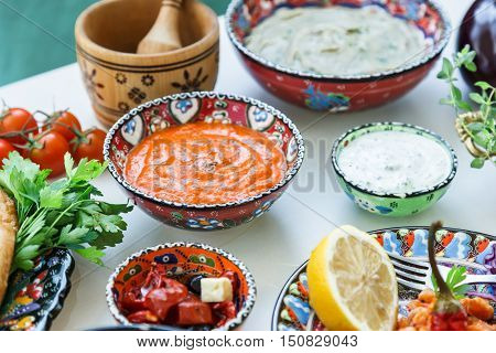 Small bowls of homemade harissa and tzatziki with meze on a table.