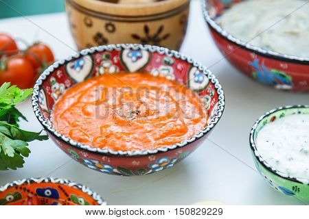 Small bowls of homemade harissa and tzatziki with meze on a table