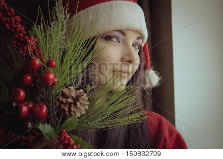 Pretty young girl in Santa's clothes posing with christmas tree branch in her hands.