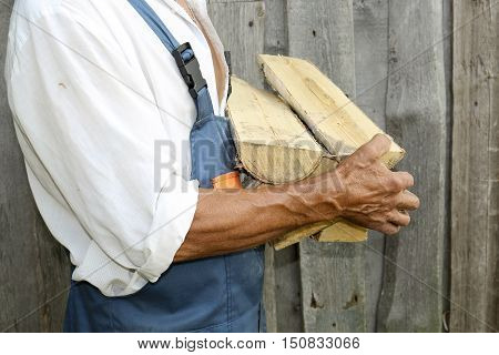 Male worker holding a large chopping wood. Birch firewood in his hands.Employees.