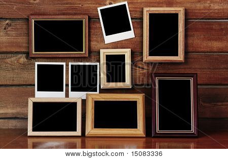 old photo frames on the wooden wall and table