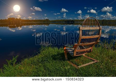 Romantic Wooden Chair on a Lake shore at Colorful Sunset