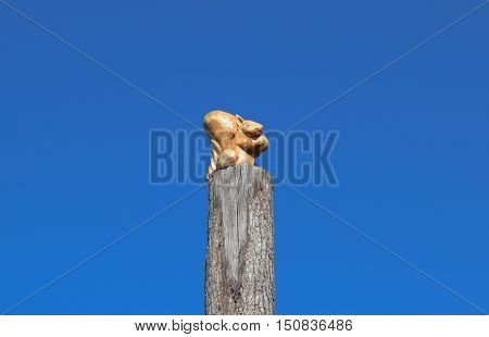 Figurine Squirrel With A Nut From A Tree On A Tree Stump On A Background Of Blue Sky. Figures Of Ani