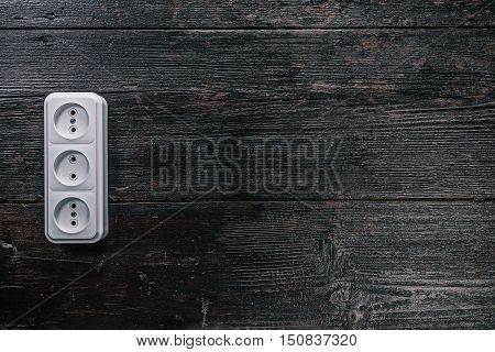 White triple electric socket on the dark wooden surface