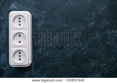 White triple electric socket on the spotty black surface