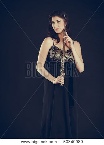 Music performance. Stunning elegant young lady with transverse flute instrument on black. Woman preparing to her solo show in theater opera.
