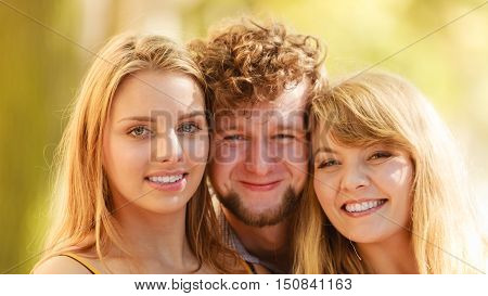 Three happy smiling young people friends outdoor. Attractive women and handsome man portrait. Summer vacation.