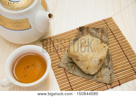 traditional Chinese glutinous rice dumpling with cup of tea and teapot horizontal composition