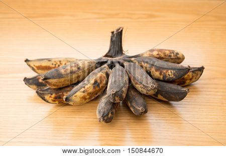 bunch of black overripe bananas on a wooden background