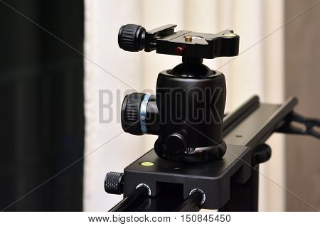 Tripod ball head mounted on linear camera slider.