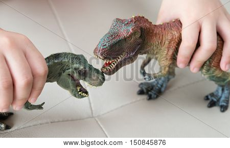 kids playing two tyrannosaurus toys on a sofa at home