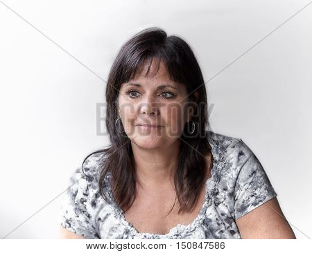 Mature smiling woman sitting and gazing out