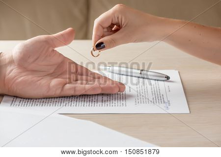 Divorce: hands of wife and husband signing divorce documents, woman returning wedding ring