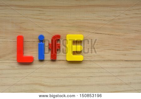 Top Lay Of The Word Life On A Wooden Background