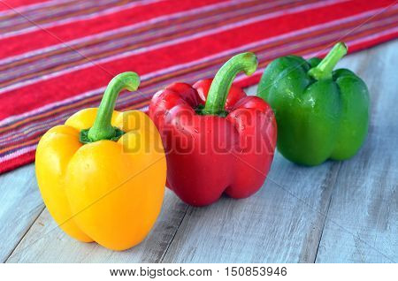Yellow, Red And Green Capsicum On A Wooden Table