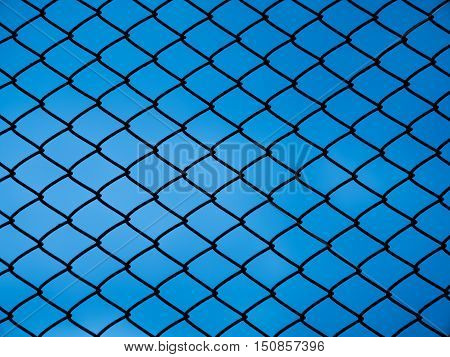 Chain link fence with blue sky for background