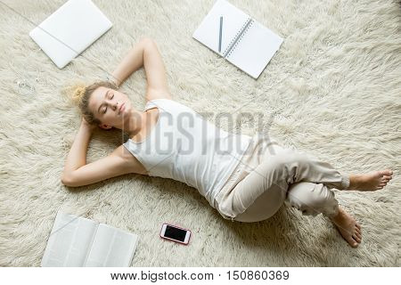 Beautiful young woman holding hands behind head while lying on white carpet on the floor in living room and sleeping after working on laptop or studying at home. Top view full length image