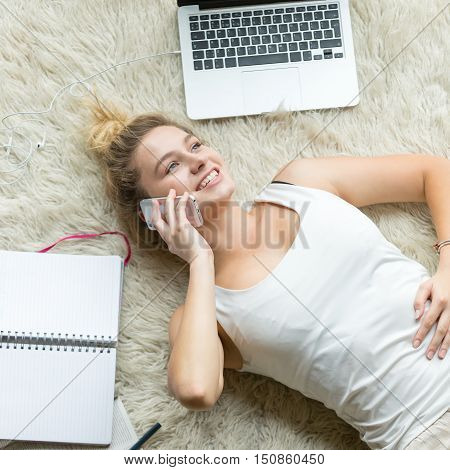 Portrait of beautiful happy smiling young woman making pleasant call, chatting on phone while lying on white floor carpet at home, studying and relaxing at home. Top view square image