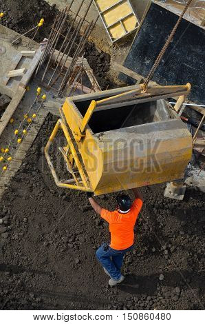 Construction Site Worker During Concrete Pouring Into Formwork